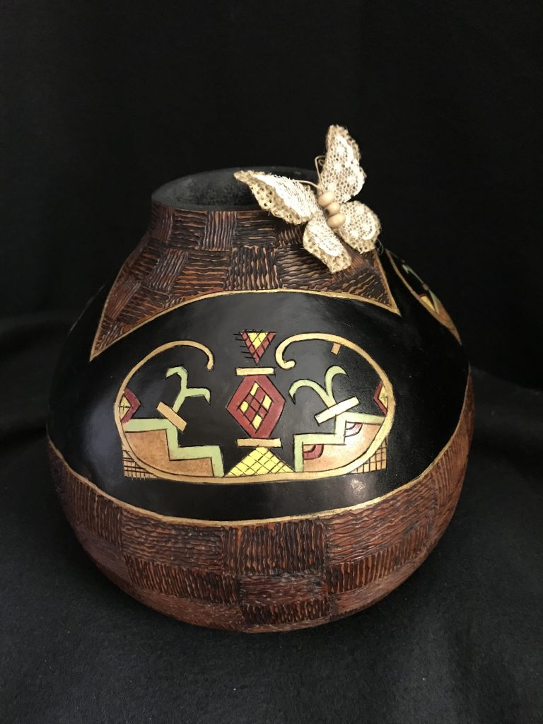 Image of gourd with artistic double curve design and a butterfly.