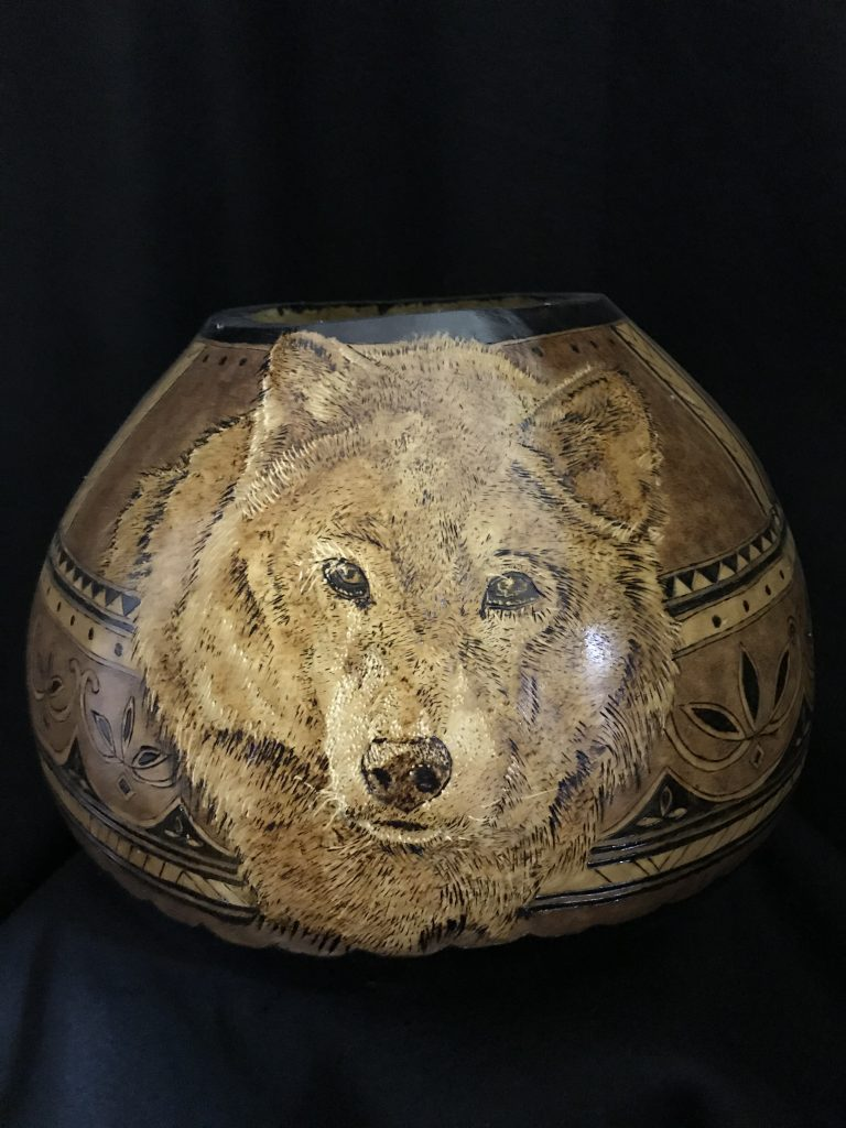 Image of painted wolf and traditional Abenaki double curve design.