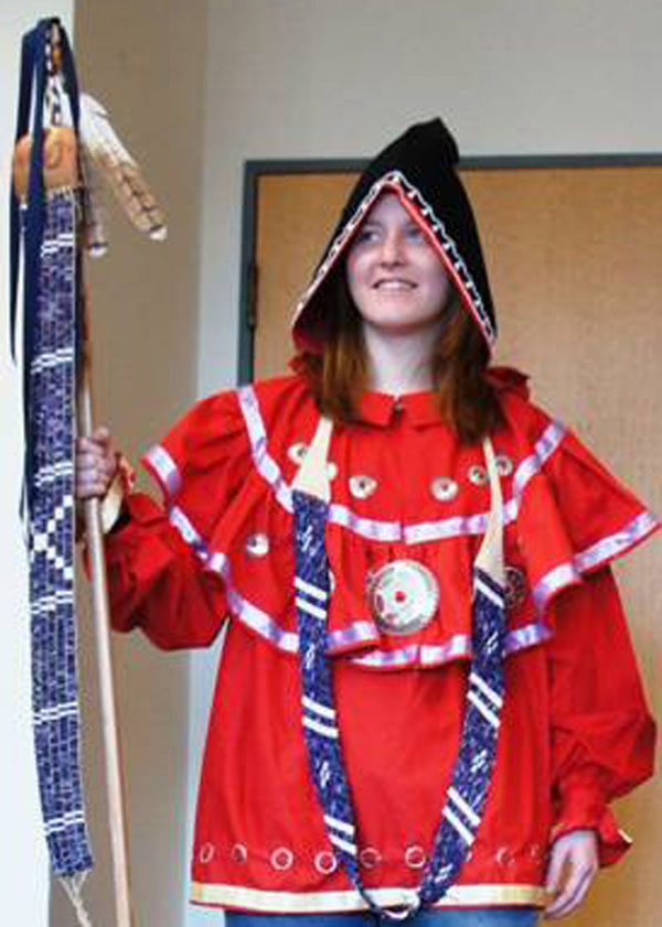 Image of girl holding staff with wampum belt made by Fred Wiseman.