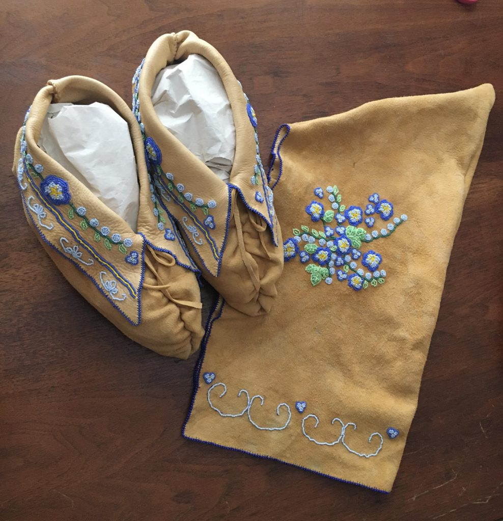 Image of beaded moccasins and peaked cap on exhibit at Burlington International Airport.