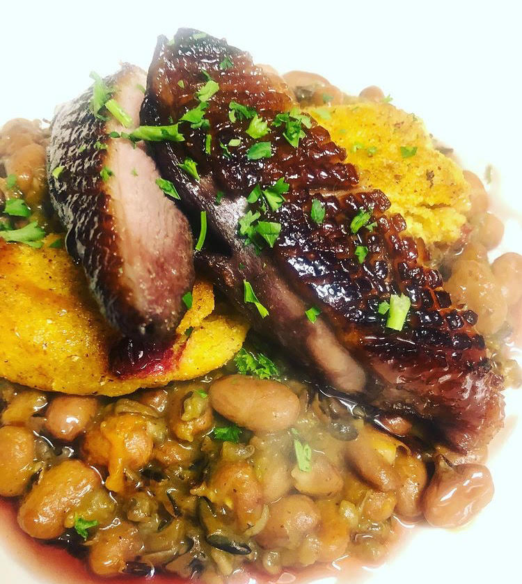 Image of Cranberry and maple cured duck breast, wild rice, Vermont cranberry bran & butternut ragout, boiled cornbread, and house blueberry and vinegar reduction.